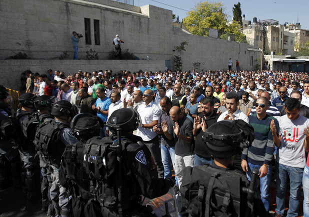 Israeli security forces stand guard as Palestinian Muslim worshipers perform traditional Friday prayers in a street outside the Old City in east Jerusalem on October 17, 2014. The Israeli government has restricted access to the mosque for men under 50 years of age.
