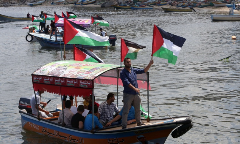 Palestinians hold their national flag as they ride boats during a rally to show support for activists on the Freedom Flotilla III at the seaport of Gaza City on 24 June 2015. The activists failed to reach Gaza, with three boats turning back and the fourth taken over by the Israelis. Photograph: Mahmud Hams/AFP/Getty Images.