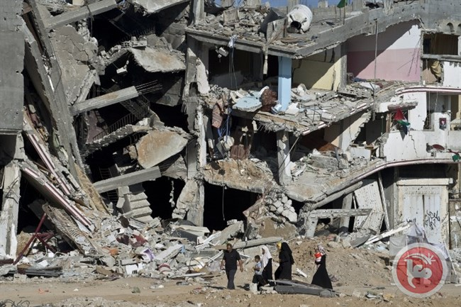 A Palestinian family walks on Aug. 27, 2014, past the collapsed remains of a building in al-Shujaiyya that was destroyed in fighting between Hamas and Israel. (AFP/Roberto Schmidt)