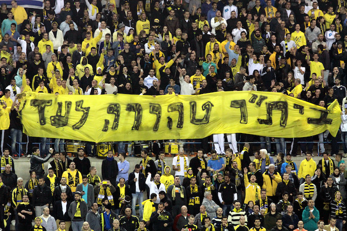 "Fans of the Beitar Jerusalem soccer team hold up a sign saying ""beitar pure for ever"" and chanted against owner Arcadi Gayadamak during Saturday evening's game against Bnei Yehuda of Tel Aviv over Gaydamak's announced intention to make two Russians the first Muslims in the teams history. Jan 26 2013. Photo by Flash90"