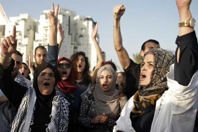 Caption: Palestinian protesters shout slogans during a demonstration on August 16, 2015 in front of the hospital in Ashkelon where Muhammad Allan is being held. (AFP/Ahmad Gharabli)