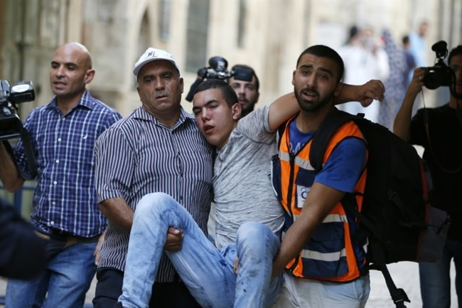 A Palestinian youth is evacuated after being injured during clashes between Palestinians and Israeli police at Jerusalem's flashpoint Al-Aqsa mosque on September 13, 2015 (AFP/Ahmad Gharabli)