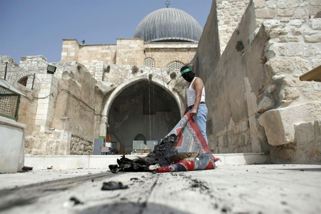 A Palestinian takes a burnt carpet out of Al-Aqsa Mosque in Jerusalem's Old City during clashes at the compound on September 13, 2015. (Photo: AFP/Ahmad Gharabli)