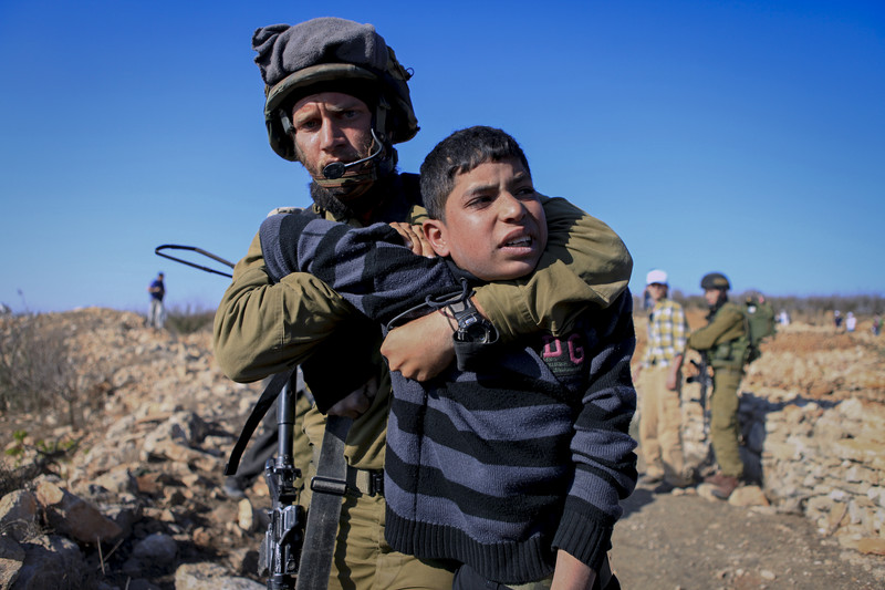 An Israeli soldier detains a child in the occupied West Bank village of Beit Ommar in 2012. Anne Paq,ActiveStills