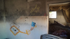 Artwork inside the burned-out Dawabshe home blames the Israeli government for the firebombing. (Mondoweiss Photo: Dan Cohen)