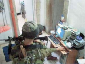 Israeli soldiers search through Palestinian computer files during a home invasion in Hebron, West Bank. Credit: Creative Commons/joshhough.