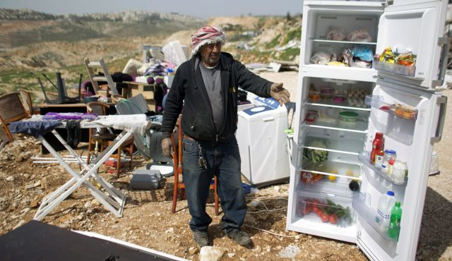 Palestinians collect their belongings after their house was demolished by Israeli bulldozers in the Arab East Jerusalem neighbourhood of Beit Hanina on March 19, 2014.