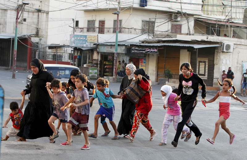 Palestinians flee clashes in Ein al-Hilweh refugee camp on 22 August. Photo: Ali Hashisho, Reuters