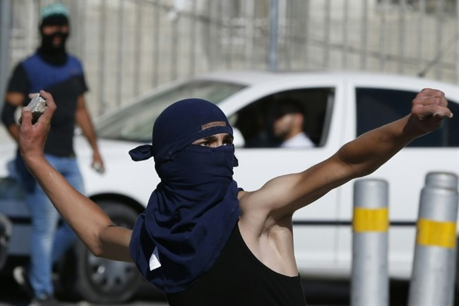 A masked Palestinian youth throws stones towards Israeli security forces during clashes at the Shuafat refugee camp in East Jerusalem on Sept. 18, 2015. (AFP/File Ahmad Gharabli)