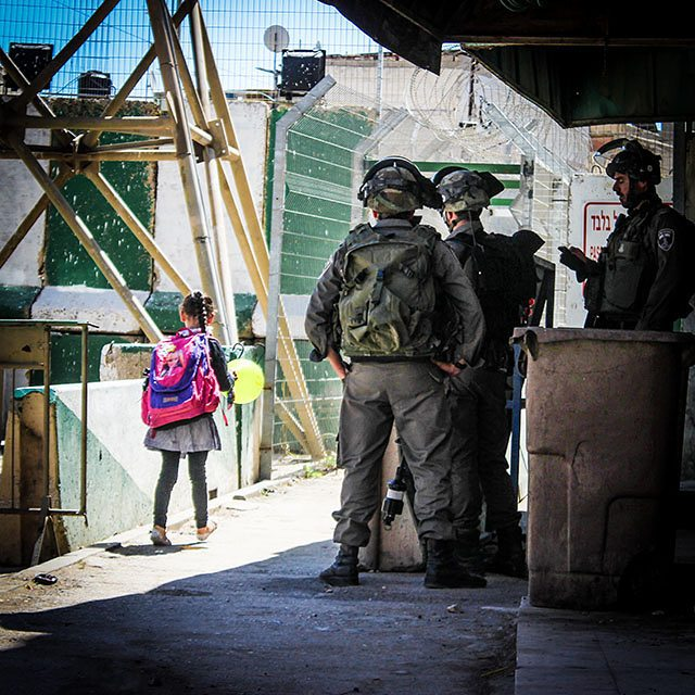 PROTECTING ISRAELI 'SETTLERS.' A little girl makes her way through Qitoun checkpoint carrying a balloon. It is the beginning of the Eid holiday (Christian Peacemaker Teams photo, 22 September 2015).