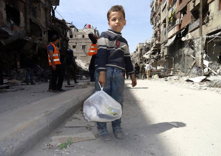 A boy holding his belongings in the besieged Yarmouk camp, south of Damascus. Thousands have reportedly fled the camp, after Isis invaded it. (Rame Alsayed/Reuters)