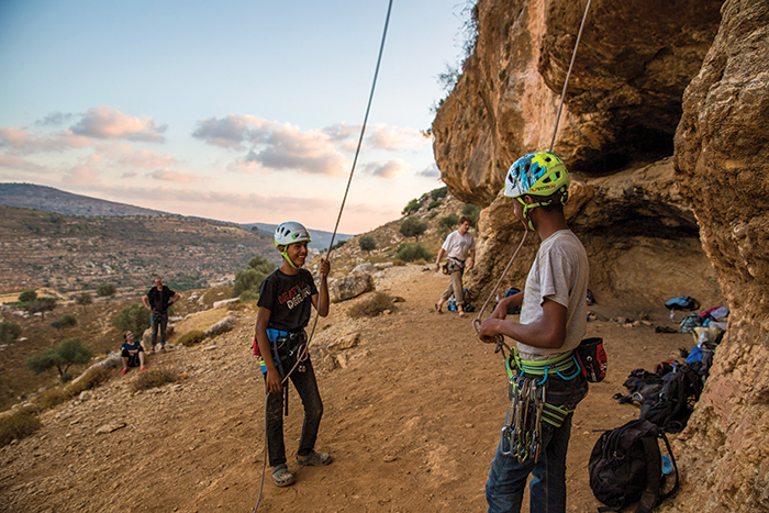 Two Bedouin boys rock climbing near their home in Ein Qiniya, a Palestinian village 4.3 miles north of Ramallah. It has existed since the Roman-era of rule in Palestine. Photo by Adam Rouhana.