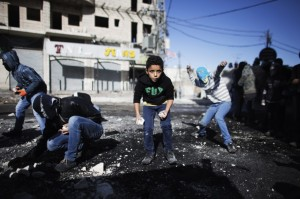 DANGEROUS TERRORISTS Palestinian youths throw stones towards Israeli border police during clashes at a checkpoint between the Shuafat refugee camp and Jerusalem November 7, 2014. REUTERS/Finbarr O'Reilly.