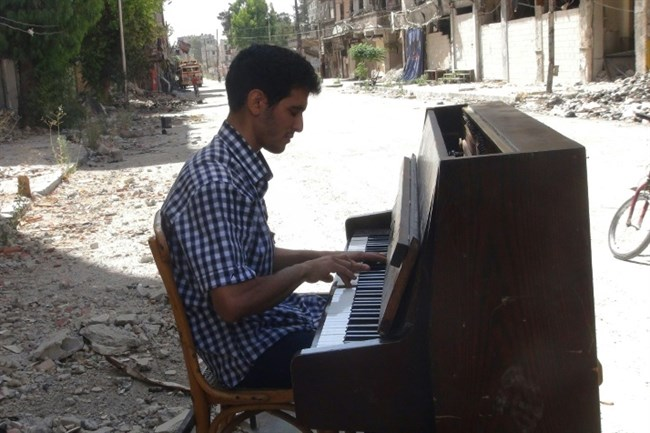 File picture shows Aeham al-Ahmad, a former resident of Damascus' Yarmouk Palestinian refugee camp, playing the piano in the street. (AFP/Rami Al-Sayed/File)