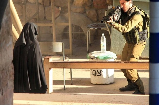 A photo of the killing shows an Israeli soldier aiming his gun at 18-year-old Hadeel al-Hashlamon. (Youth Against Settlements)