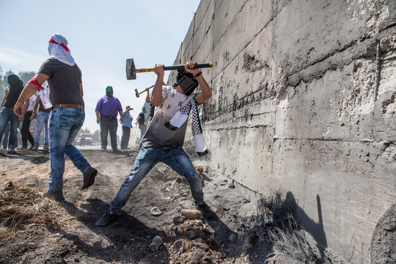 Palestinians attempt to break through a section of the separation wall Israel built in the occupied East Jerusalem neighborhood of Abu Dis, 11 October. (Photo by Yotam Ronen, ActiveStills)