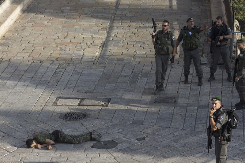 Israeli police stand near the body of a Palestinian who was shot and killed after he allegedly tried to stab a person in Jerusalem's Old City on 14 October. (Photo Oren Ziv /ActiveStills)