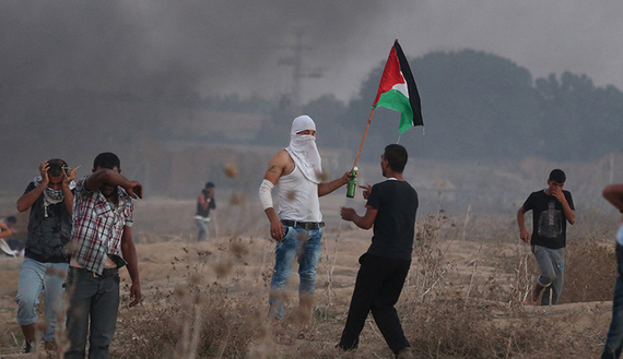 A Palestinian protester holds a Palestinian flag during clashes with Israeli troops near the border between Israel and the Gaza Strip, Oct. 15, 2015. (photo by REUTERS/Ibraheem Abu Mustafa)