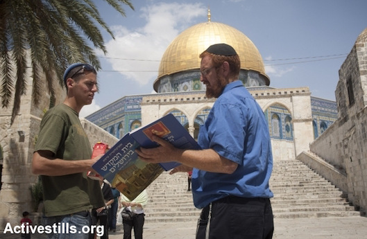Right-wing 'Temple activist' Yehuda Glick holding a book depicting the Jewish Temple while standing in front of the Aqsa Mosque in Jerusalem, May 21, 2009. Glick survived an assassination attempt by a Palestinian man in 2014. (Photo by Oren Ziv/Activestills.org)
