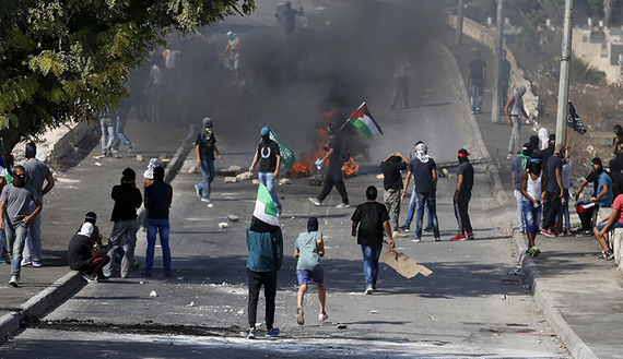 Palestinians stand near a burning barricade during clashes with Israeli security forces in the East Jerusalem neighborhood of Issawiya, Oct. 4, 2015. (photo by REUTERS/Ammar Awad)
