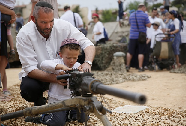 An Israeli man shows his son how to work a machine gun. (AFP PHOTO/GALI. Photo via Newscom.)
