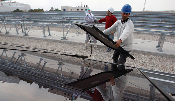 A Palestinian laborer installs solar panels at a photovoltaic plant in the West Bank city of Jericho, March 27, 2012. (photo by REUTERS/Mohamad Torokman)