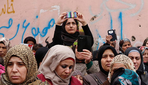 THE 'SMARTPHONE INTIFADA.' Palestinian women take pictures on smartphones during the funeral of a Palestinian man in the West Bank city of Bethlehem, Feb. 24, 2015. (photo by REUTERS/Ammar Awad)