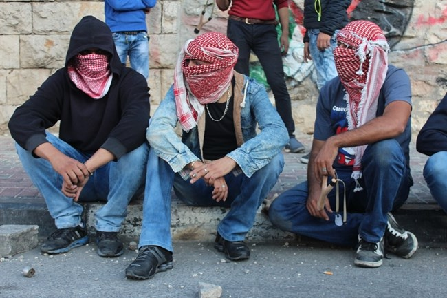 Three young Palestinian protesters sit on a pavement during clashes in Bethlehem, Oct. 9, 2015. (MaanImages/Killian Redden/File) Number ❶ below.