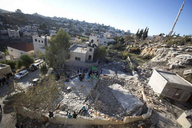 Palestinians inspect a house that was demolished by the Israeli army in the village of Silwad, near the West Bank city of Ramallah, Saturday, Nov. 14, 2015. The Israeli military says it has demolished the homes of four Palestinians who allegedly carried out deadly attacks against Israelis. (Photo: Majdi Mohammed, AP)