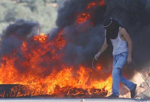 Palestinian protesters burn tires during clashes with Israeli security forces following the funeral of Abdul Rahman Barghouthi