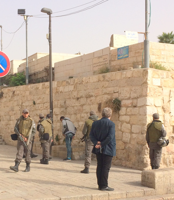 Israeli Soldiers stop and search young Palestinian man while a member of a Sabeel Ecumenical Liberation Theology delegation looks on. (Photo: Harold Knight, Nov. 12, 2015)