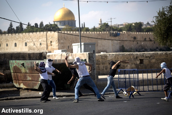 File photo of Palestinian youths throwing stones toward Israeli police in the East Jerusalem neighborhood of Ras al-Amud in response to Israeli-imposed restrictions on access to the Aqsa Mosque. (Oren Ziv/Activestills.org)
