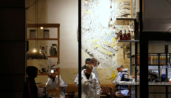Israeli policemen work inside a restaurant following a shooting attack that took place in the center of Tel Aviv