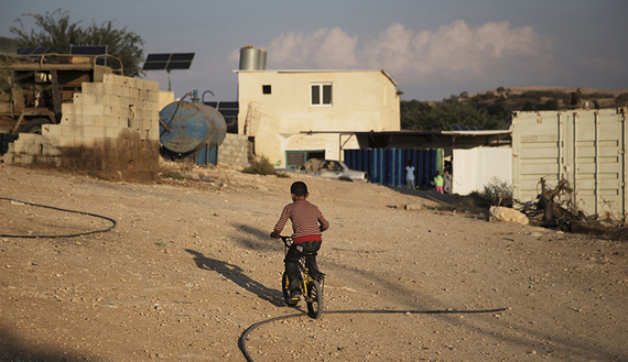 Bedouin boy rides his bike in southern Israel's Negev desert