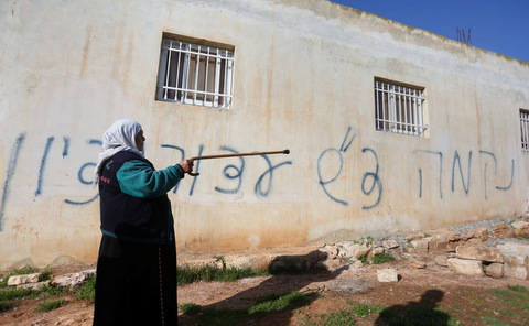 "A Palestinian woman stands next to a house sprayed with graffiti reading in Hebrew: ""revenge"" and ""hello from the prisoners of Zion"", in the village of Beitillu, near Ramallah"