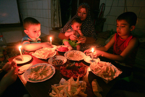 .A Palestinian family eats dinner by candlelight at their makeshift home in the Rafah refugee camp, in the southern Gaza Strip, during a power outage on June 12, 2017. (Abed Rahim Khatib/ Flash90, from +972 Magazine)