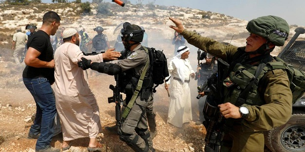 Israeli soldier throws a sound grenade during a scuffle with Palestinian demonstrators in the village of Ras Karkar