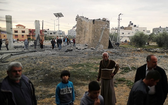 Palestinians gather around the remains of a building that was destroyed by an Israeli air strike, in Khan Younis in the southern Gaza Strip